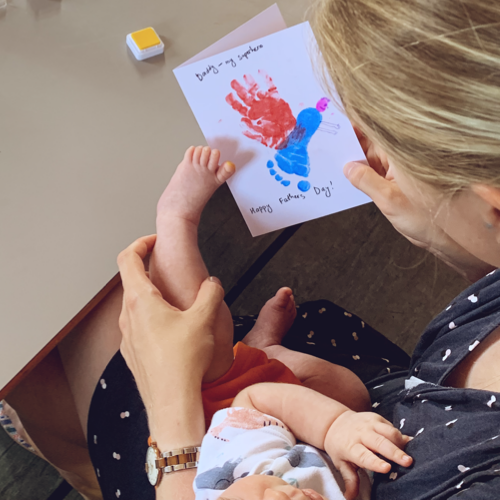 Mother and baby printing a fathers' day card that reads Daddy - my superhero and features the babies hand and foot prints